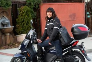Debra Chin on motorcycle with Lauren bag